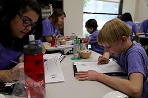 A Teacher guides a student through an assignment on a shared desk