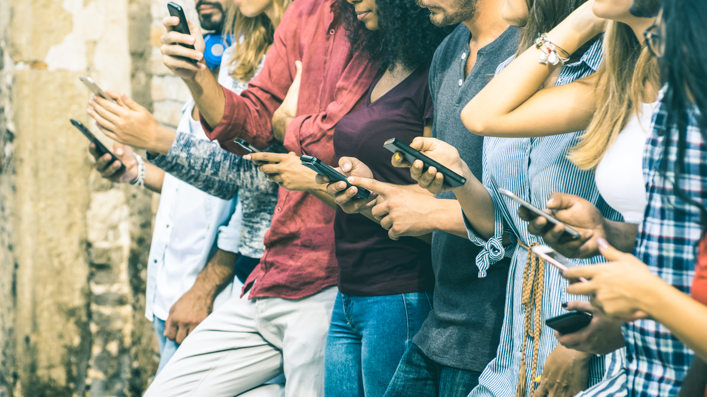 Stock photo of a row of people all on their smart phones