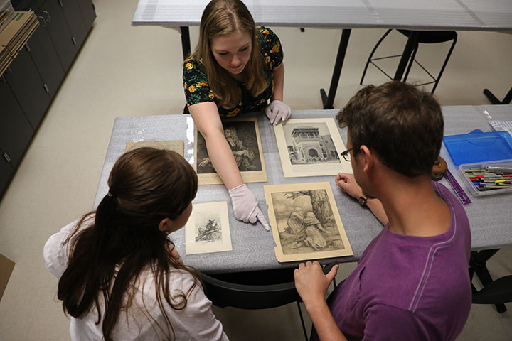Students in Prof. Rachael Nadeau Johnson's collections management course work with museum objects in the collections lab.