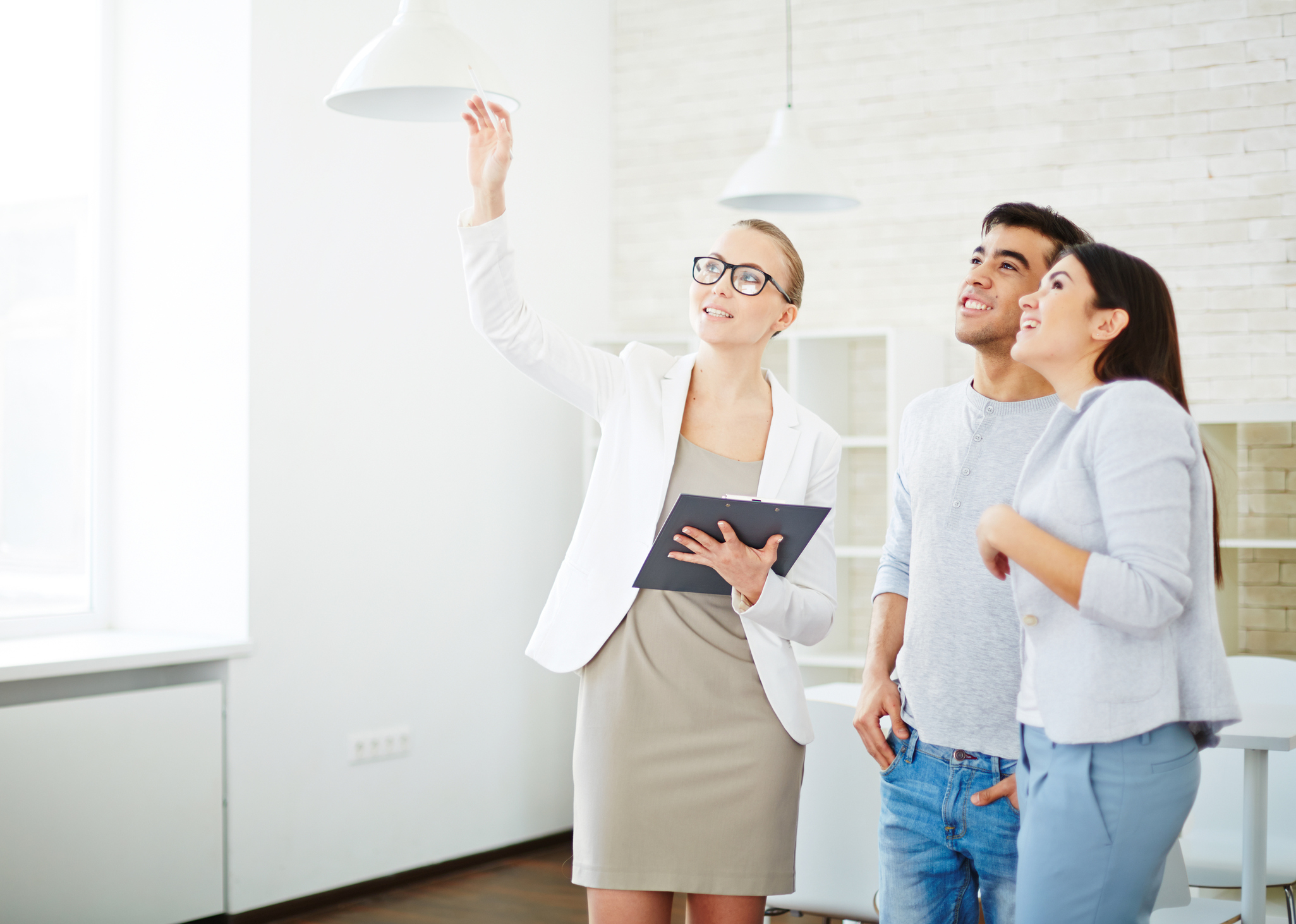 Stock photo of a relator showing a space to a young couple
