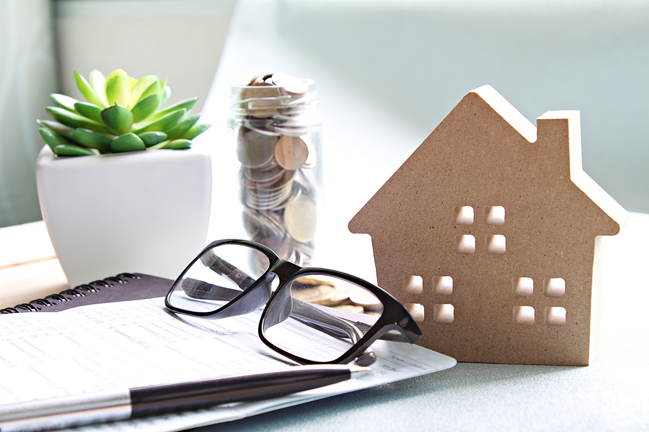 Stock Photo of a house model, eyeglasses and paperwork