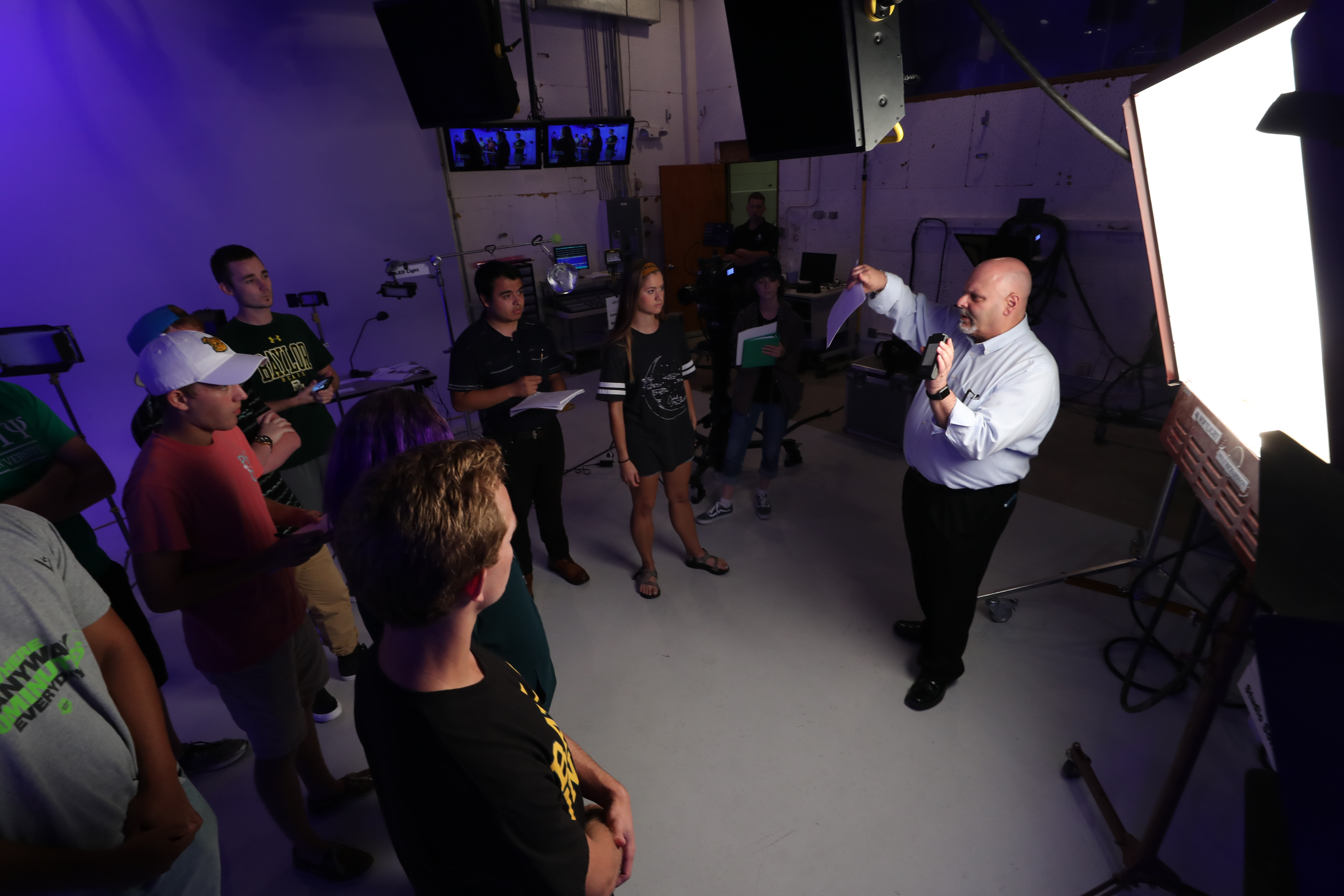 A professor guides students in a studio