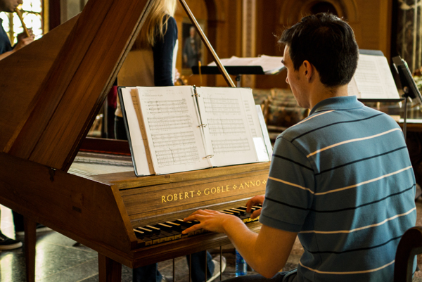 a School of Music student sits at a grand piano and practices