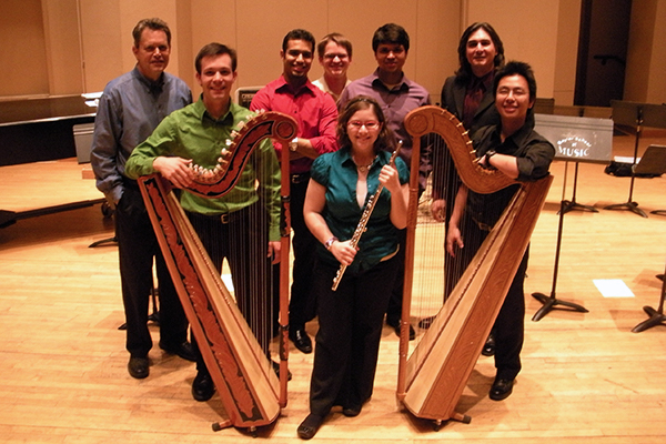 Framed by two harps, an ensemble group faces the camera