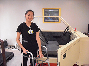 An occupational therapist demonstrates how one uses a walker to get into a car