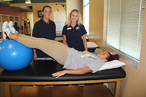 Two students guide a patient through physical therapy drills