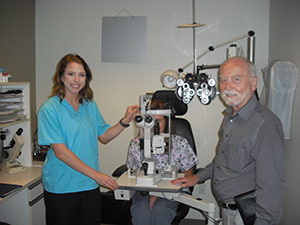 An optometry student learns from a teacher in front of optical equipment