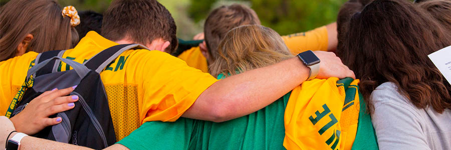 Group Photo of People arm in arm and dressed in Baylor colors