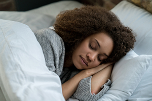 Photo of a young lady laying her head on a pillow to sleep