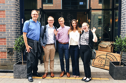 A cohort gathers in front of a coffee shop in the UK