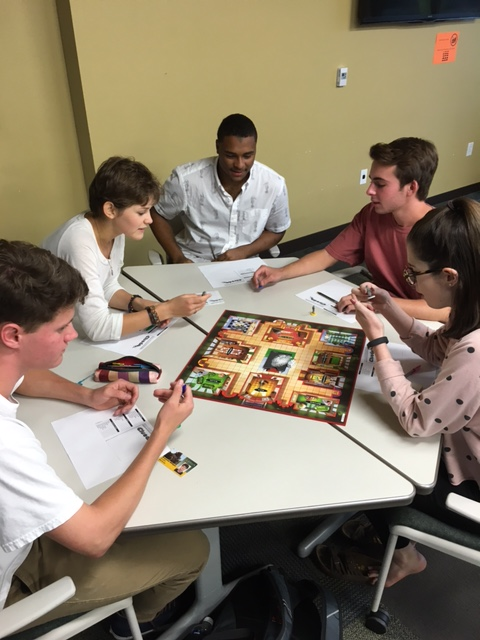 Students gathered around a board game at a table