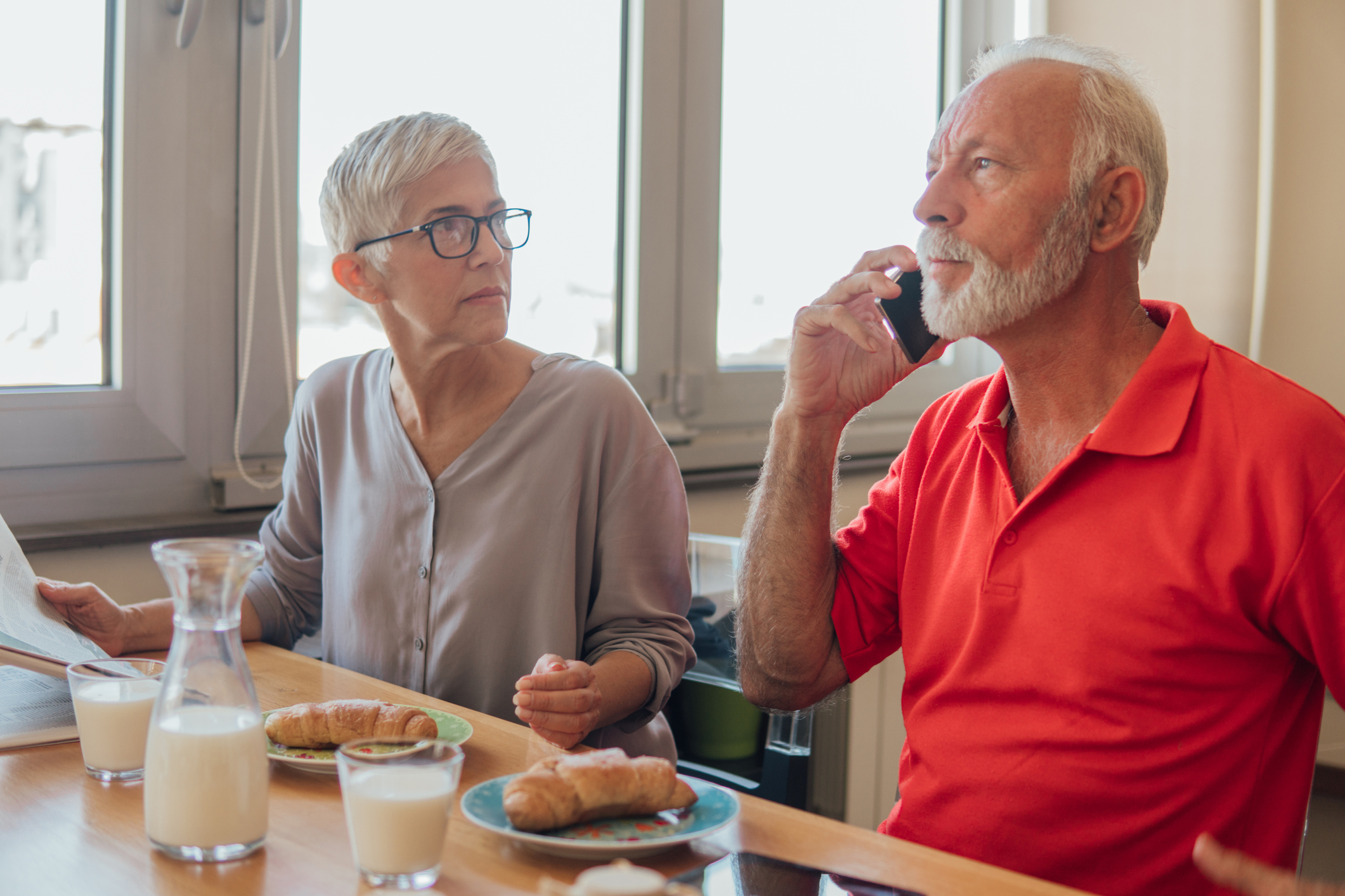 Stock photo of a man and a woman at a meal, with the man on his cell phone