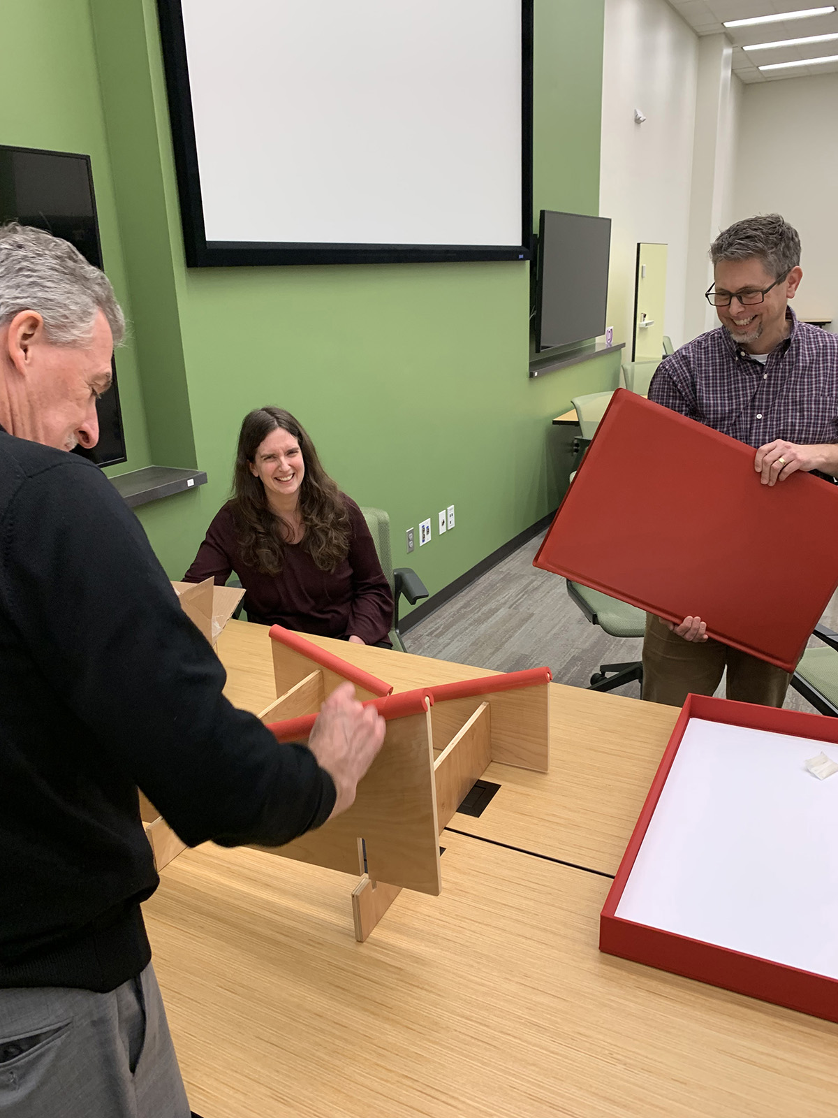 John Wilson, Andrea Turner (Central Libraries Special Collections) and Sha Towers (Interim Associate Dean for Central Libraries) set a volume of the St. John's Bible on a viewing stand