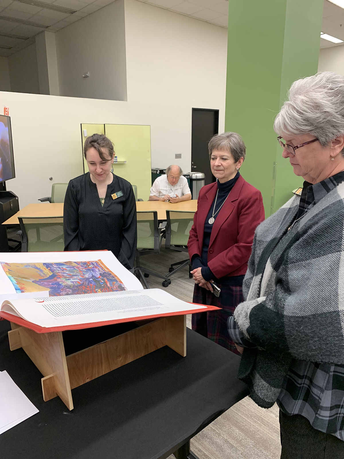 Amy Runyon, Kathy Hillman and Lori Evers view a volume of the St. John's Bible Heritage Edition