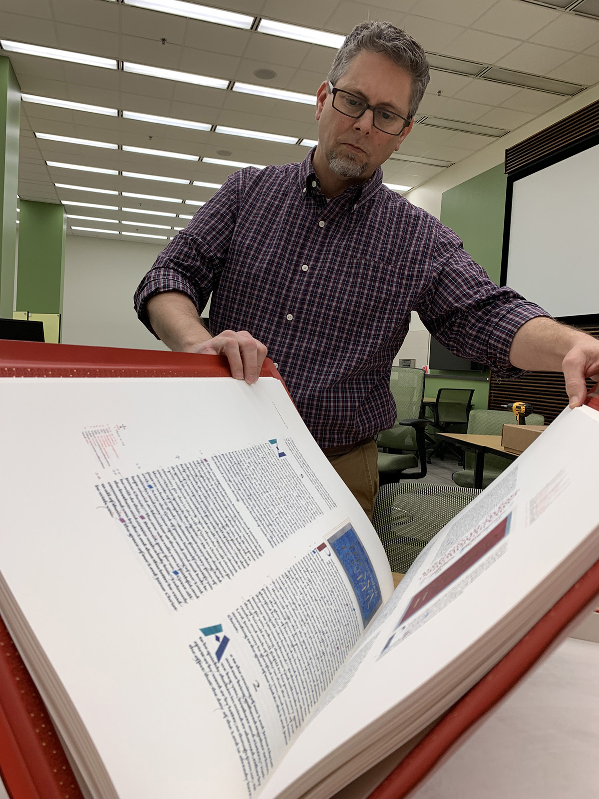 Interim Associate Dean for University Libraries Sha Towers opens a volume from the St. John's Bible Heritage Edition