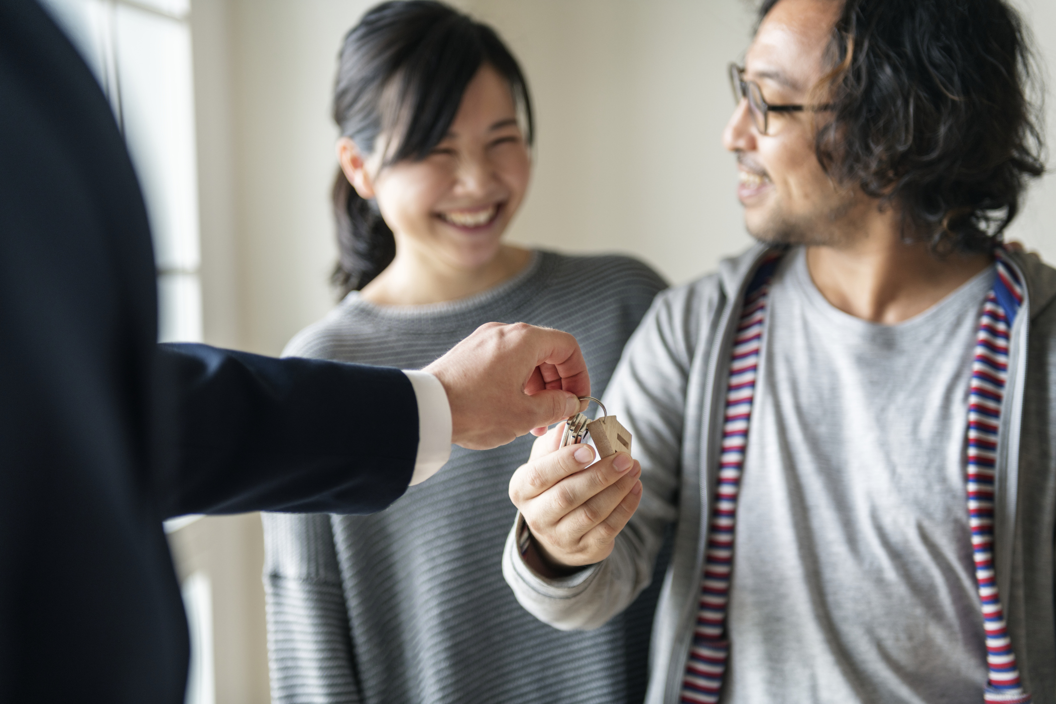 Stock photo of a couple receiving house keys from a realtor