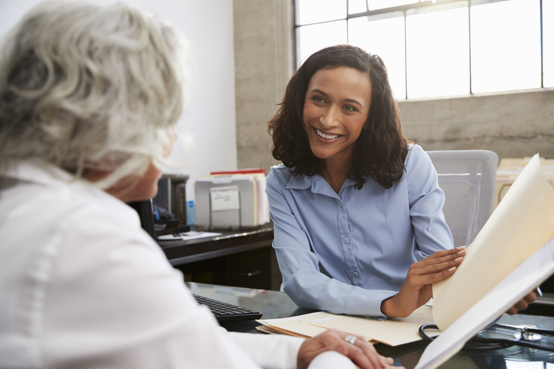 Stock photo of a woman smiling and drawing a customer's attention to paperwork