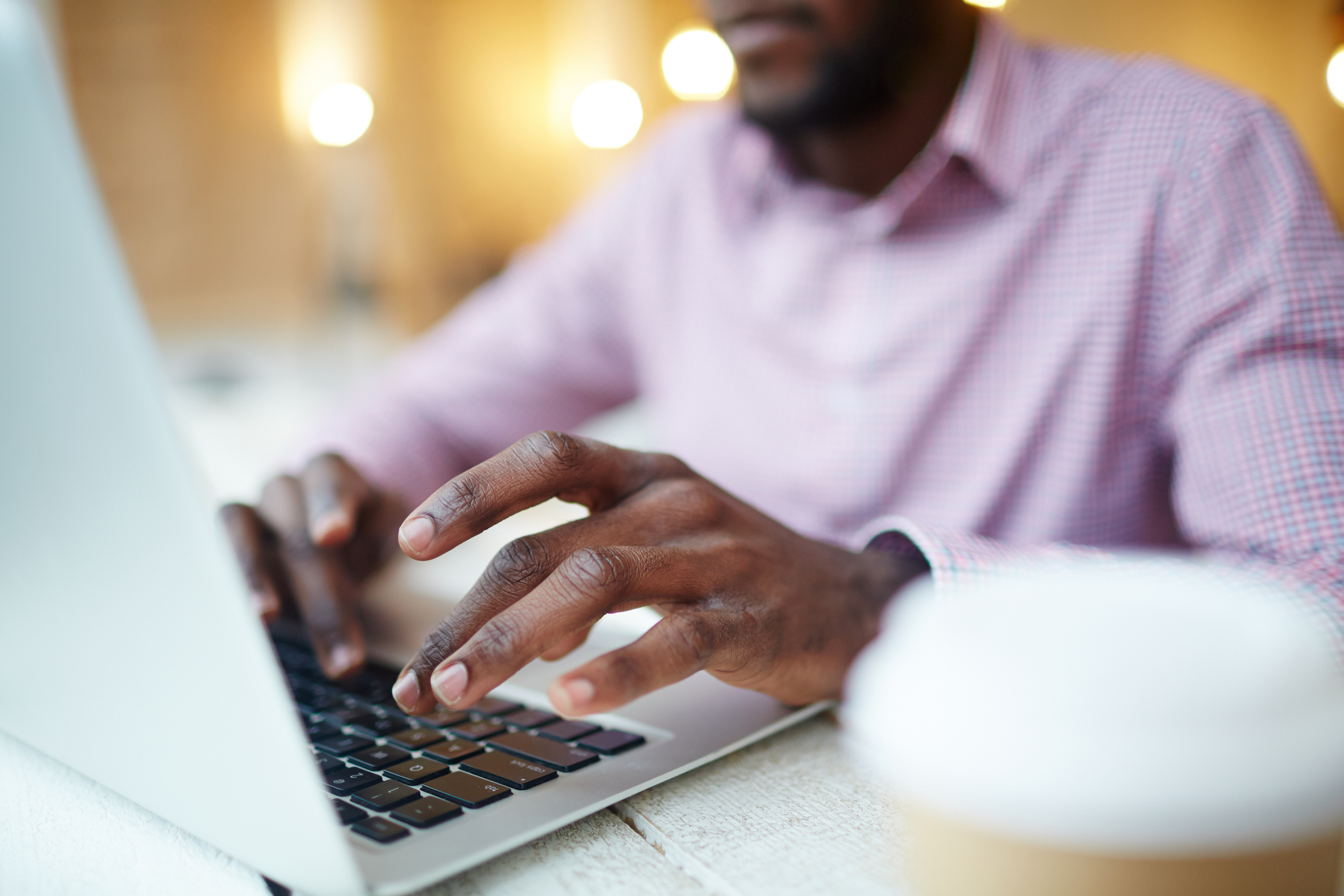 Stock photo of a man typing on a laptop computer