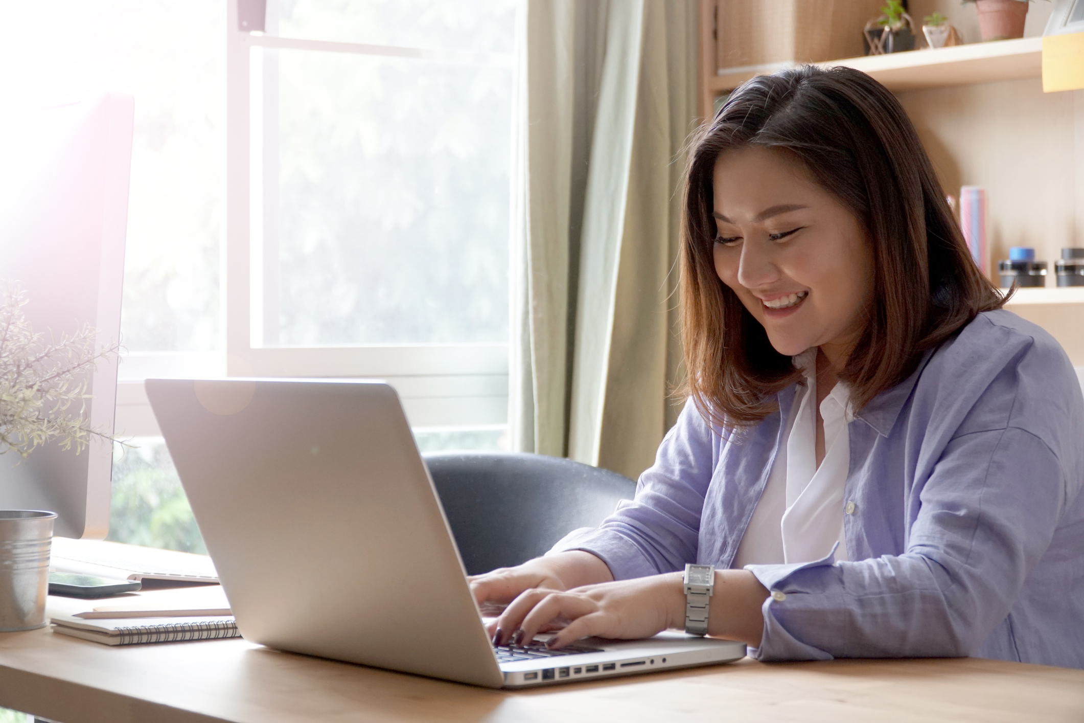Stock photo of woman at laptop, smiling