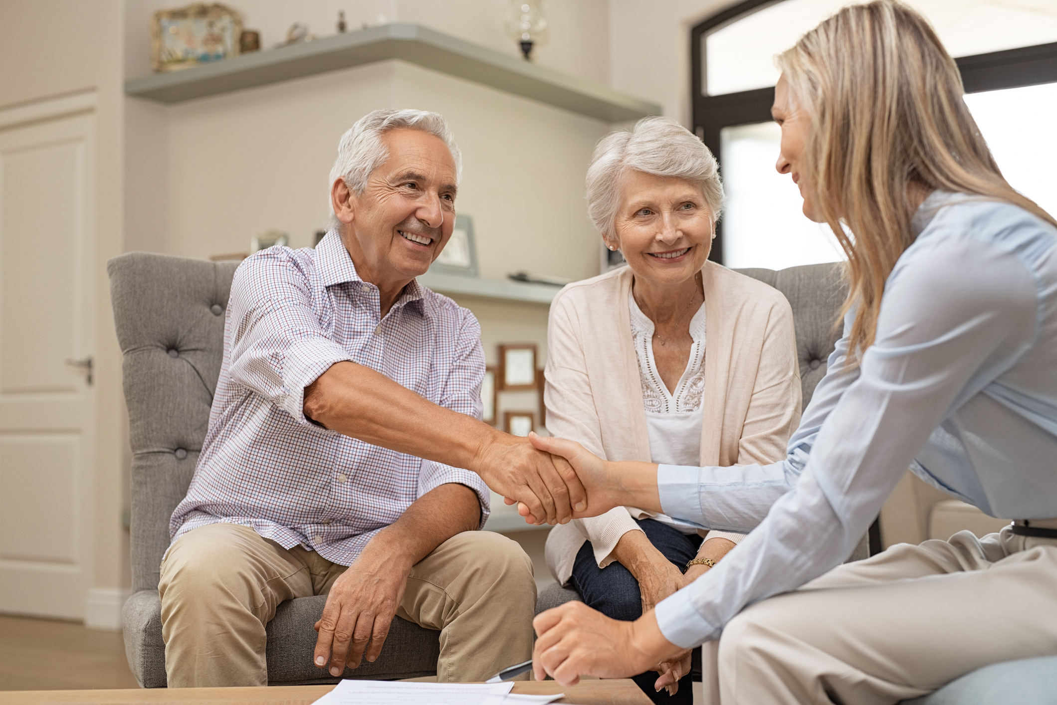 Stock photo of an older couple shaking hands with a young realtor