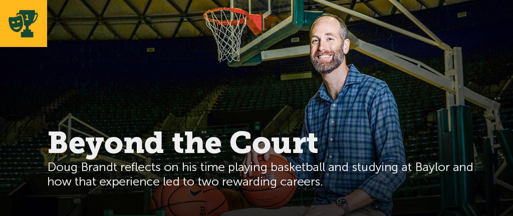 Former Baylor basketball player Doug Brandt sits in a chair on the Ferrell Center court next to a practice rack of basketballs.