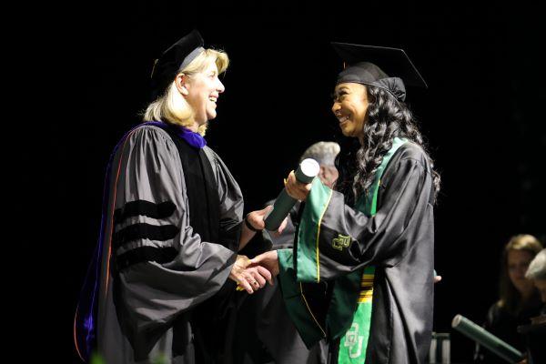 President Livingstone congratulating graduating student
