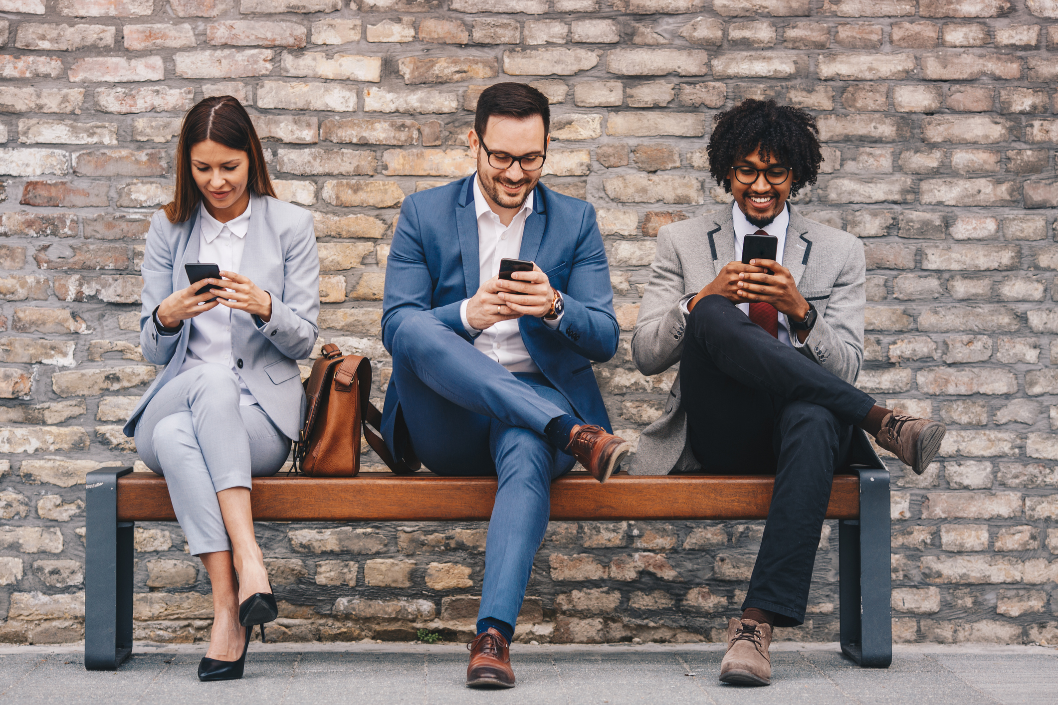 stock photo of two men and one woman in business attire, looking at their respective smart phones