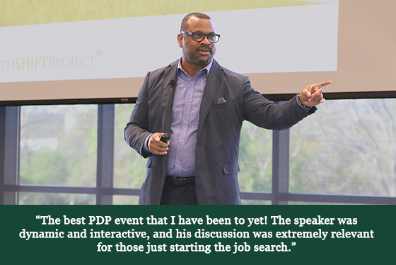 A man speaking on stage with a quotation that says, 'The best PDP event that I have been to yet! The speaker was dynamic and interactive, and his discussion was extremely relevant for those just starting the job season.'