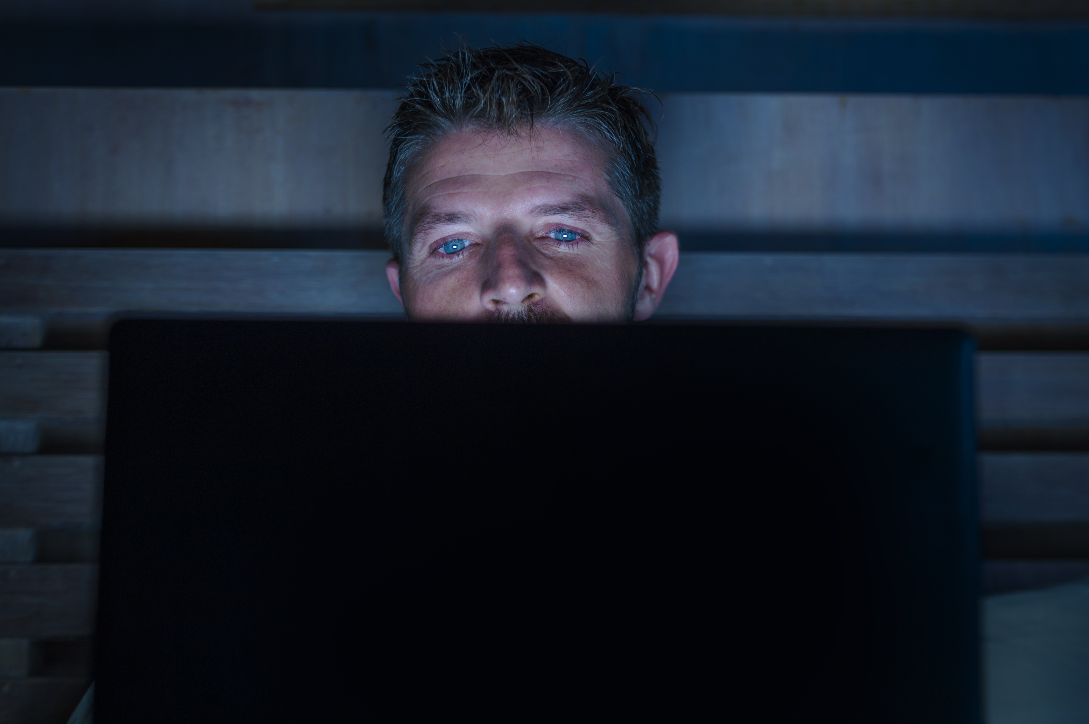 man looking at computer screen while sitting in the dark