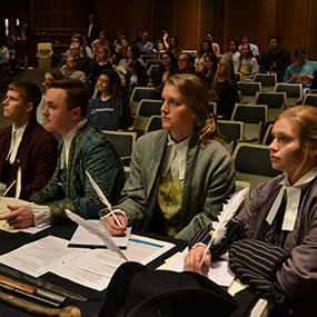 Students in period costumes sit attentively at the lecture