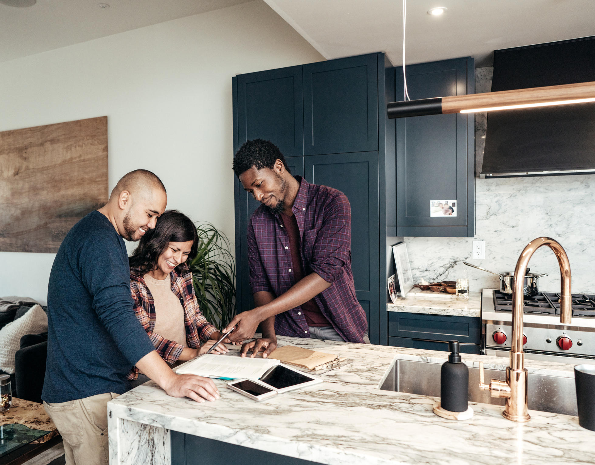 stock photo of realtor showing a couple paperwork while standing in a new kitchen