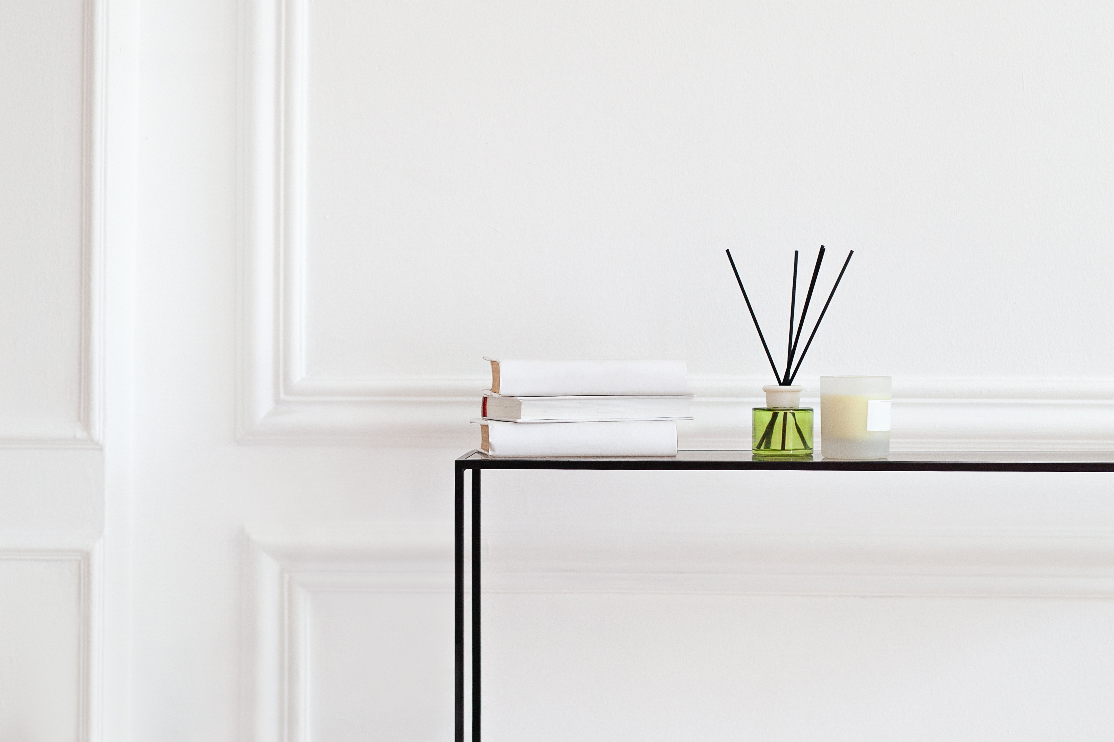 stock photo of white hallway with white books and aromatherapy and essential oils on a simple clean line table