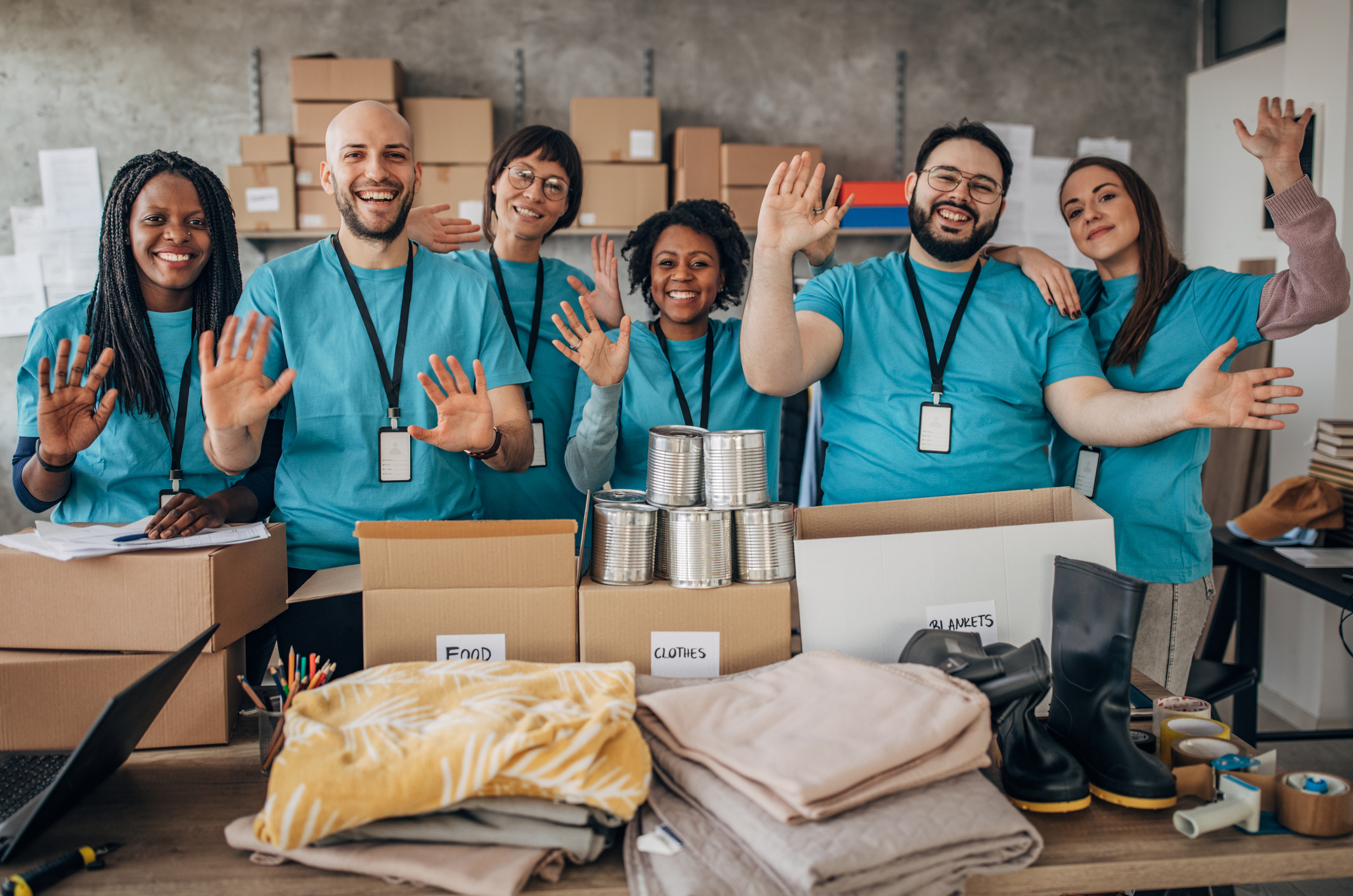 stock photo of six team members in the same t-shirts packing food boxes
