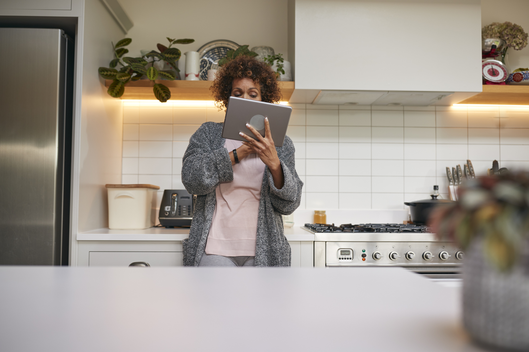 woman standing in kitchen while looking at and scrolling tablet