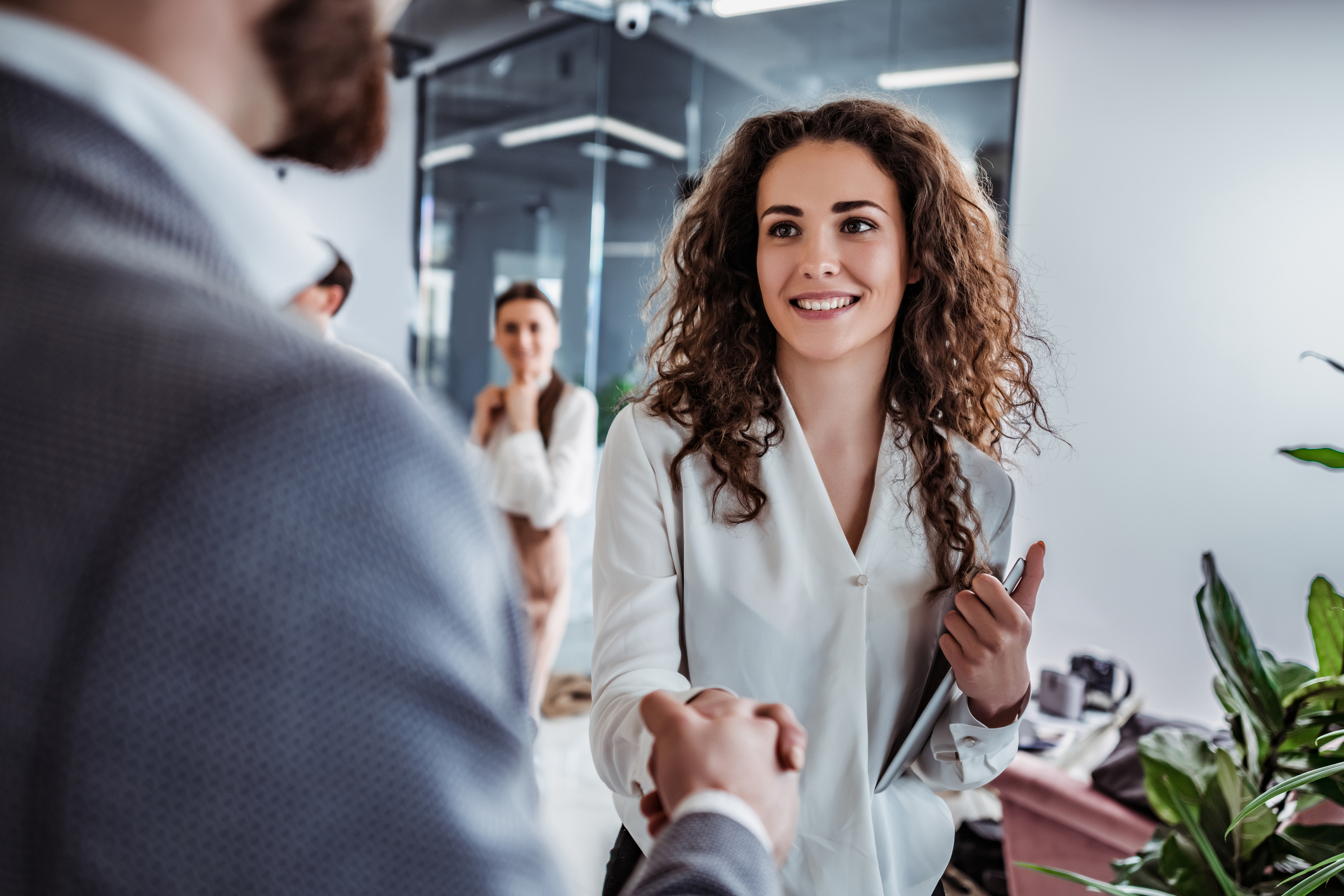 stock image of woman shaking hands with colleague