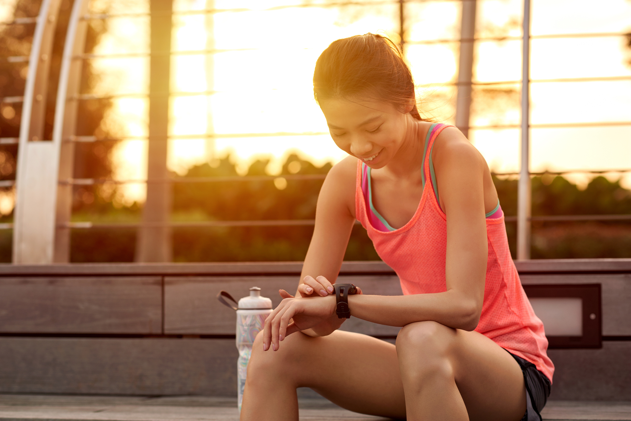 stock photo of woman in exercise attire checking her watch after a run