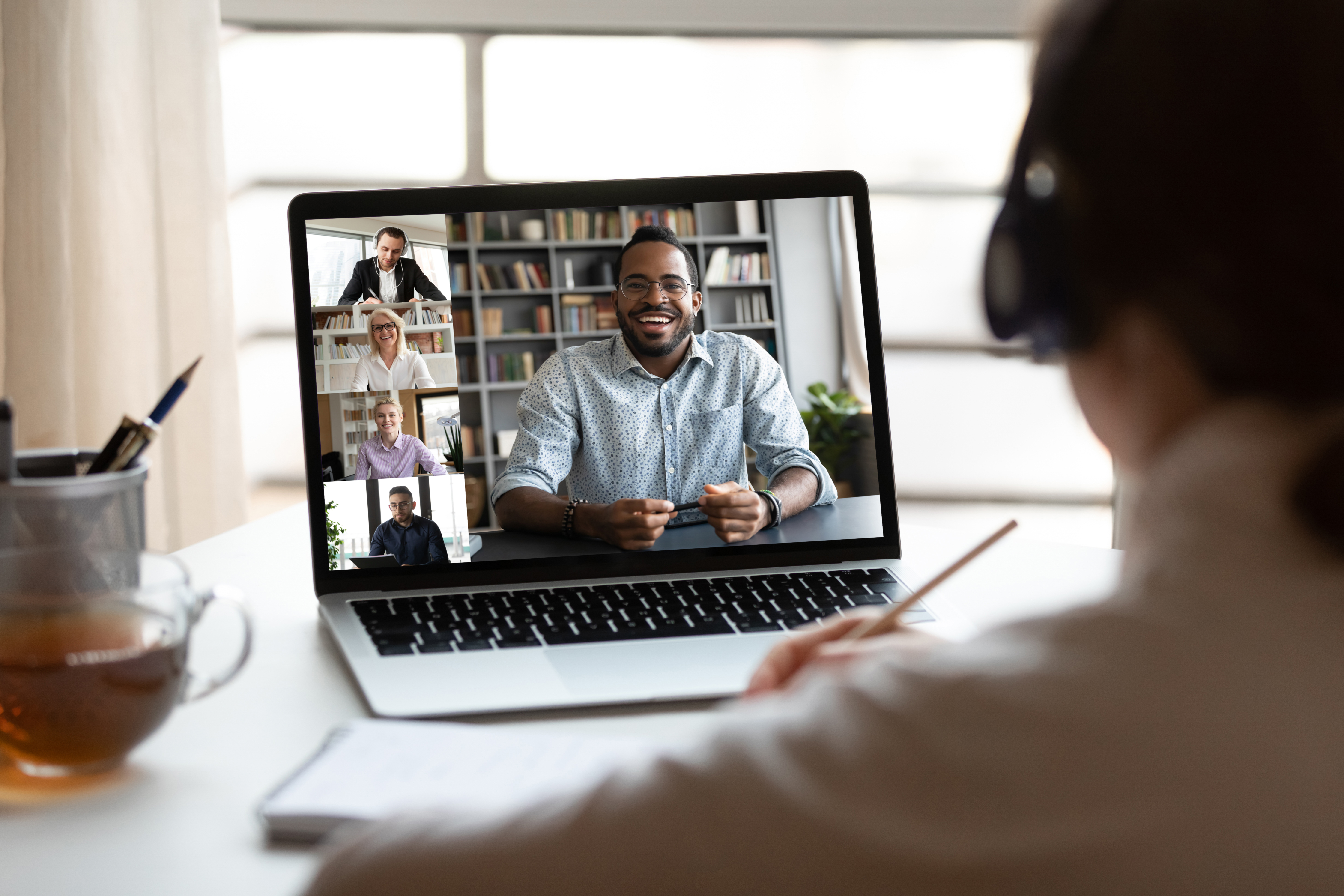 stock image looking over someone's shoulder at zoom call on laptop screen