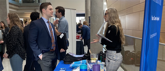 Male student and a woman talking at a career fair booth