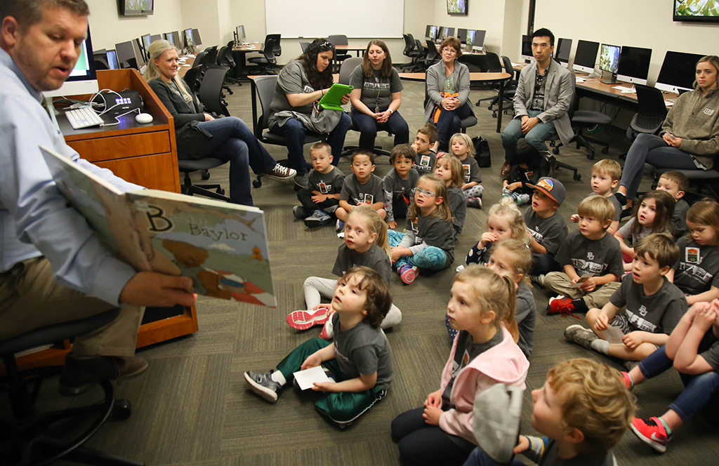 A teacher reads a book out loud to a classroom of students