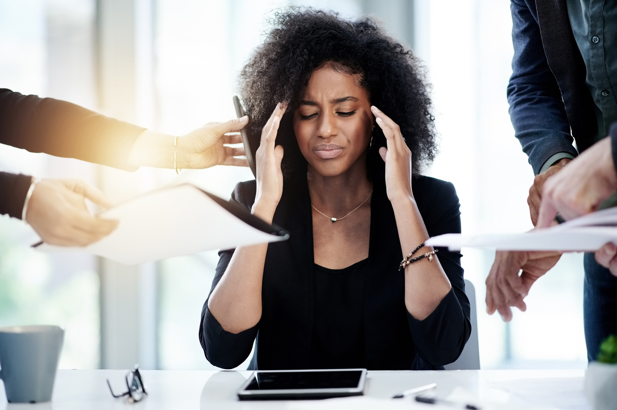 stock photo of woman holding head in pain while other hands reach in handing her a phone, pen, and paper