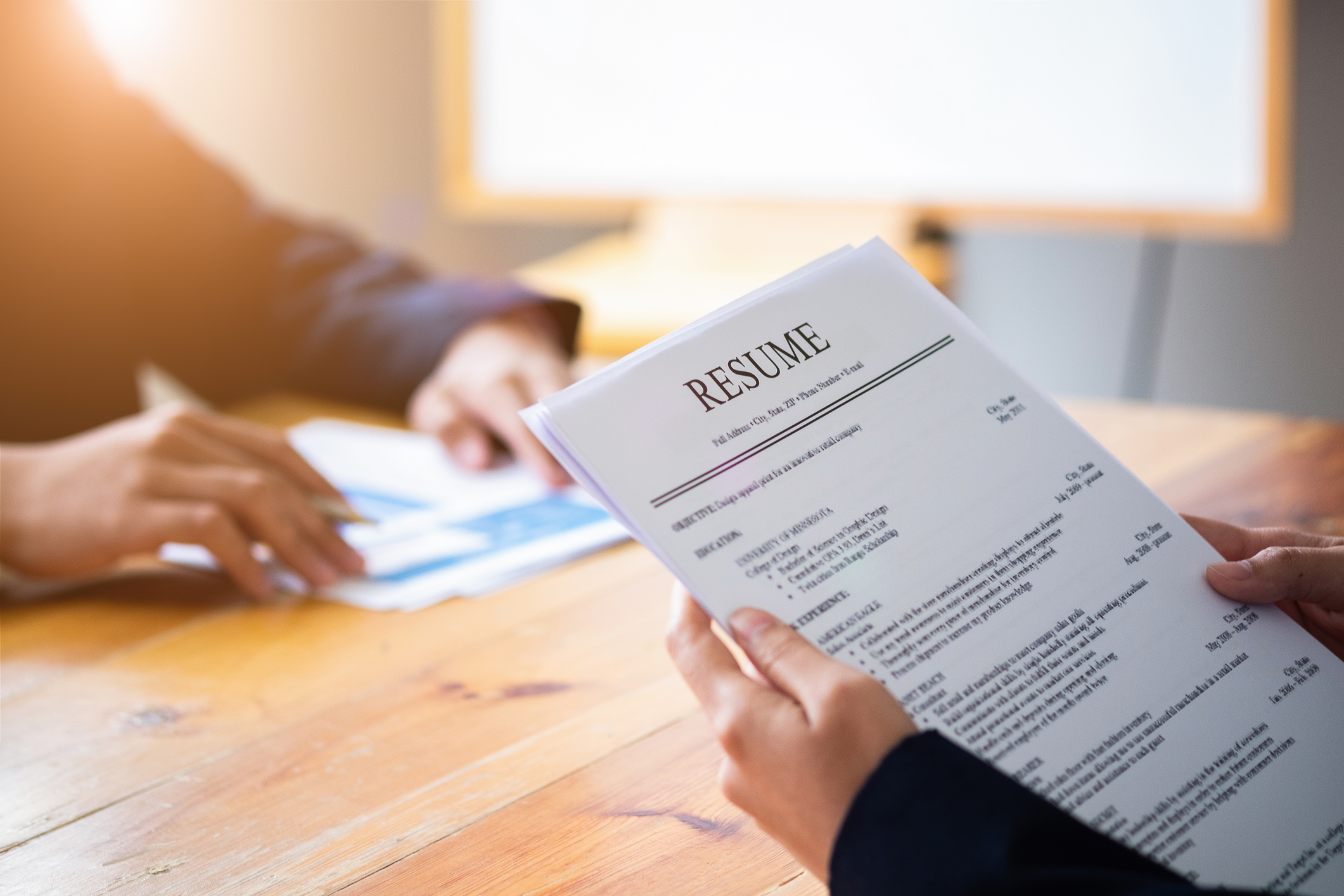 stock photo of persons hands holding a resume and sitting across from an interviewer