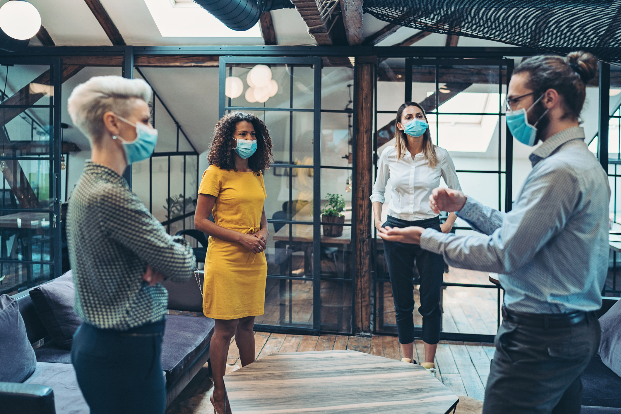 stock photo of four employees standing in a circle in a meeting and wearing masks