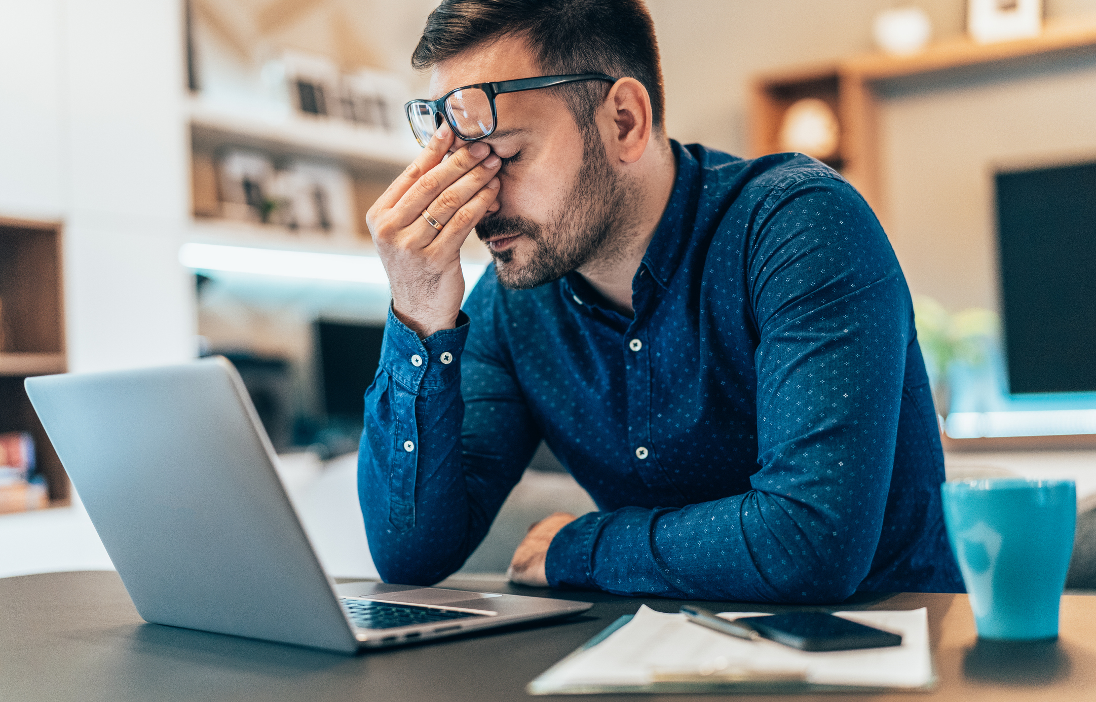man working in front of laptop and rubbing eyes in frustration