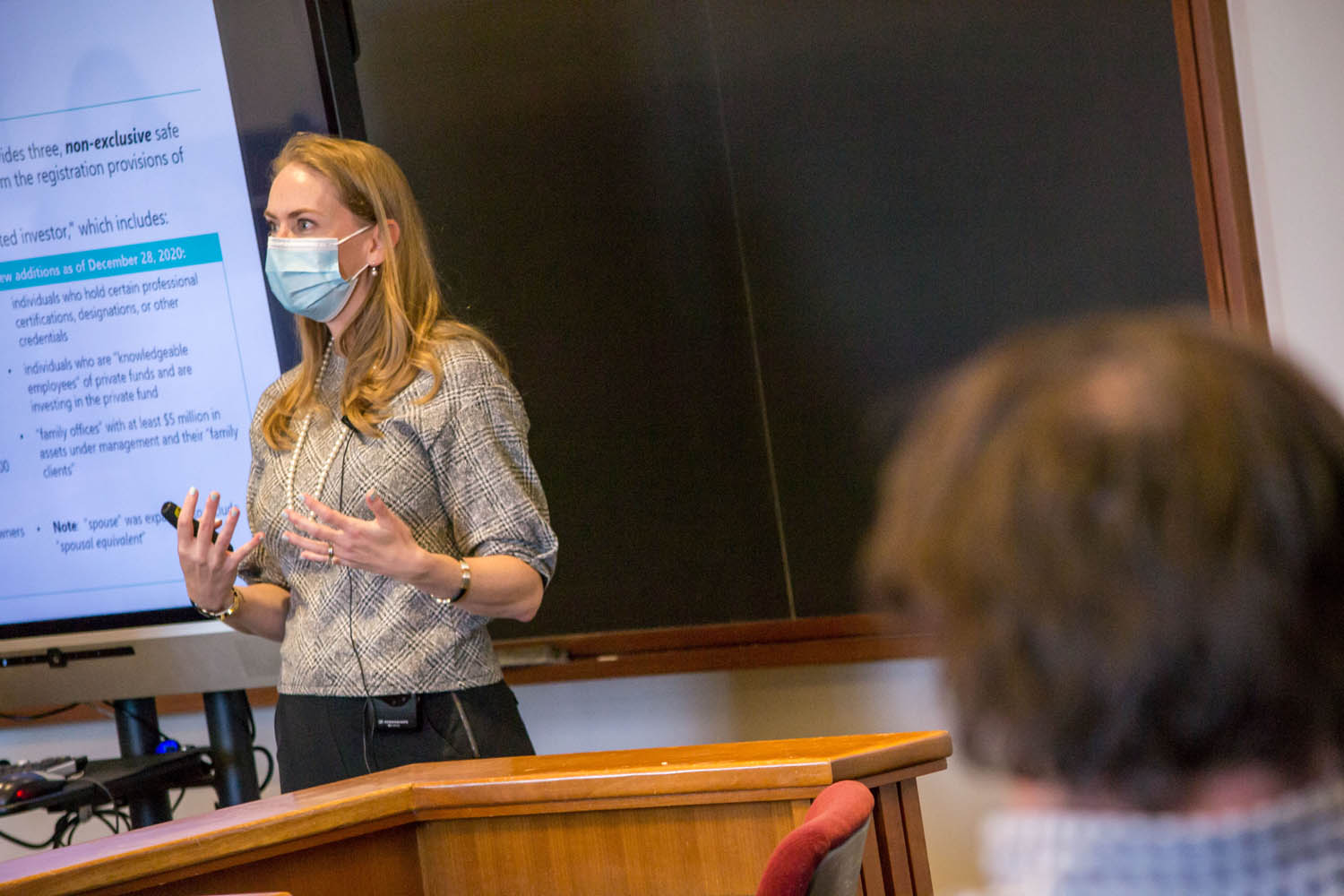 Professor lecturing in mask at front of classroom