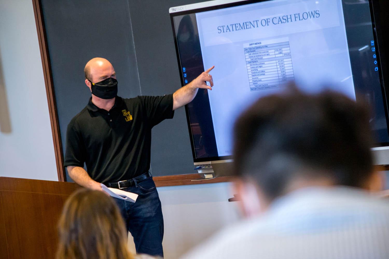Professor in black polo leading audio/visual lecture