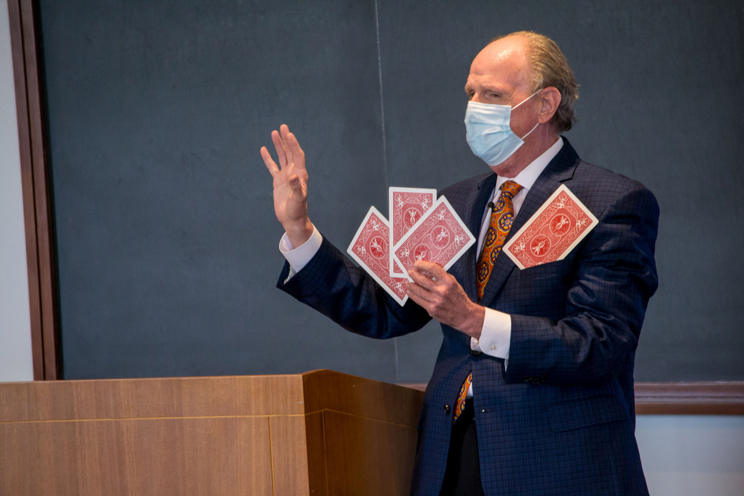 Professor teaching with oversize playing cards at front of classroom