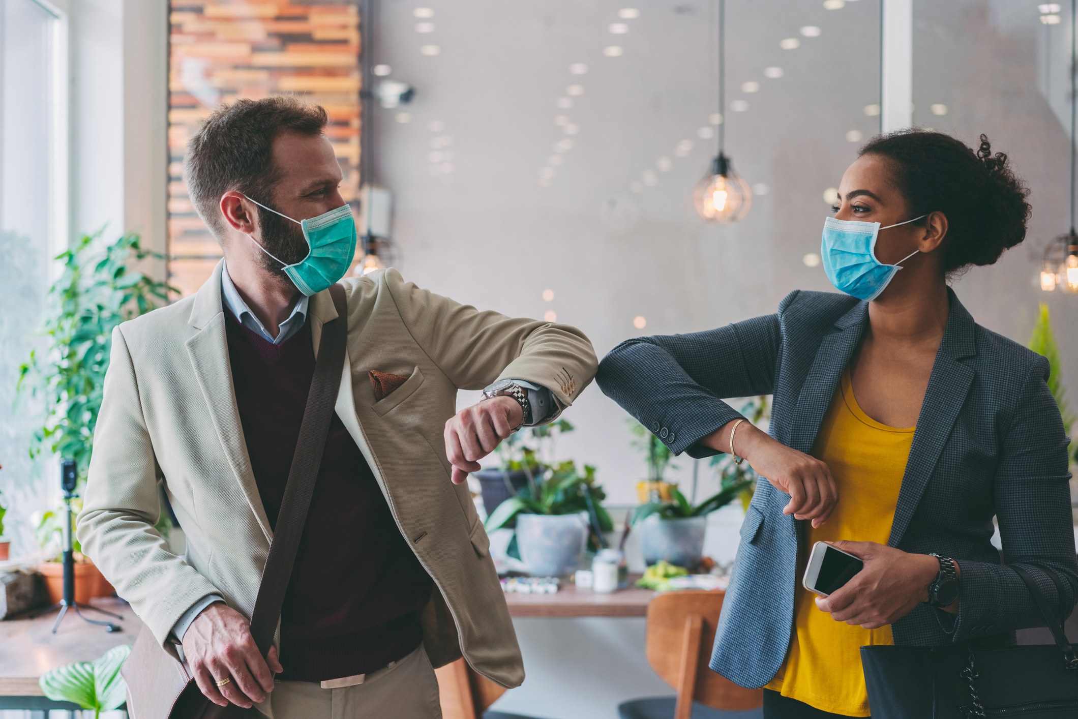 Stock photo of two colleagues in facemasks bumping elbows in place of a high five