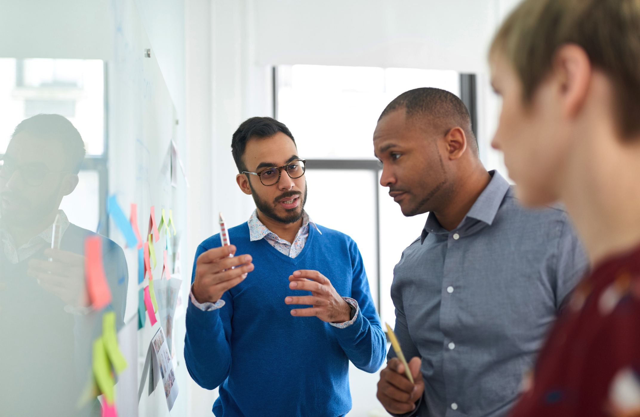 Stock photo of three colleagues looking at white board on the wall. One is holding a marker and explaining a concept while the others look on