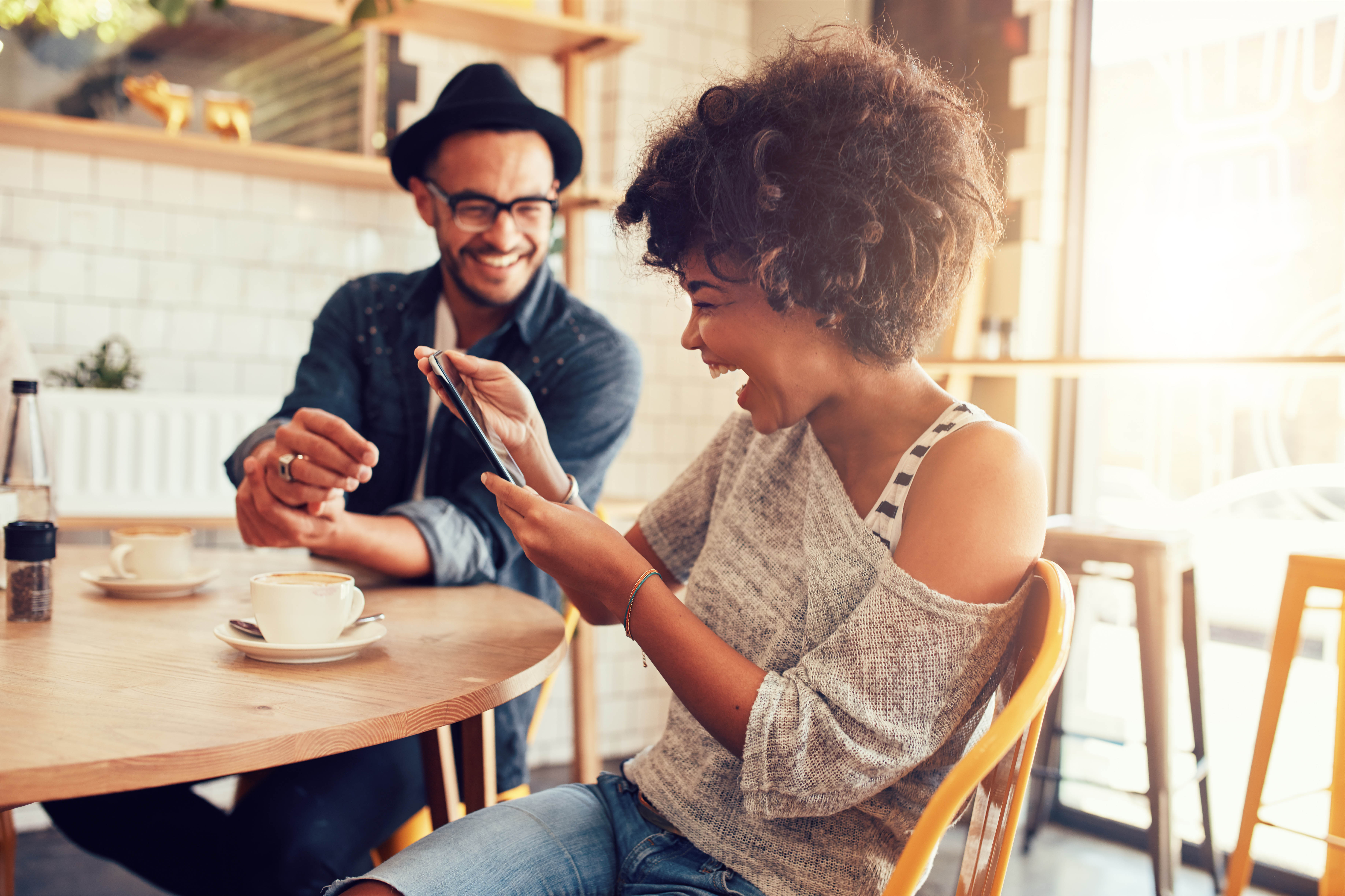 Stock photo of a man and woman drinking coffee at a table and and looking at and laughing at her cell phone