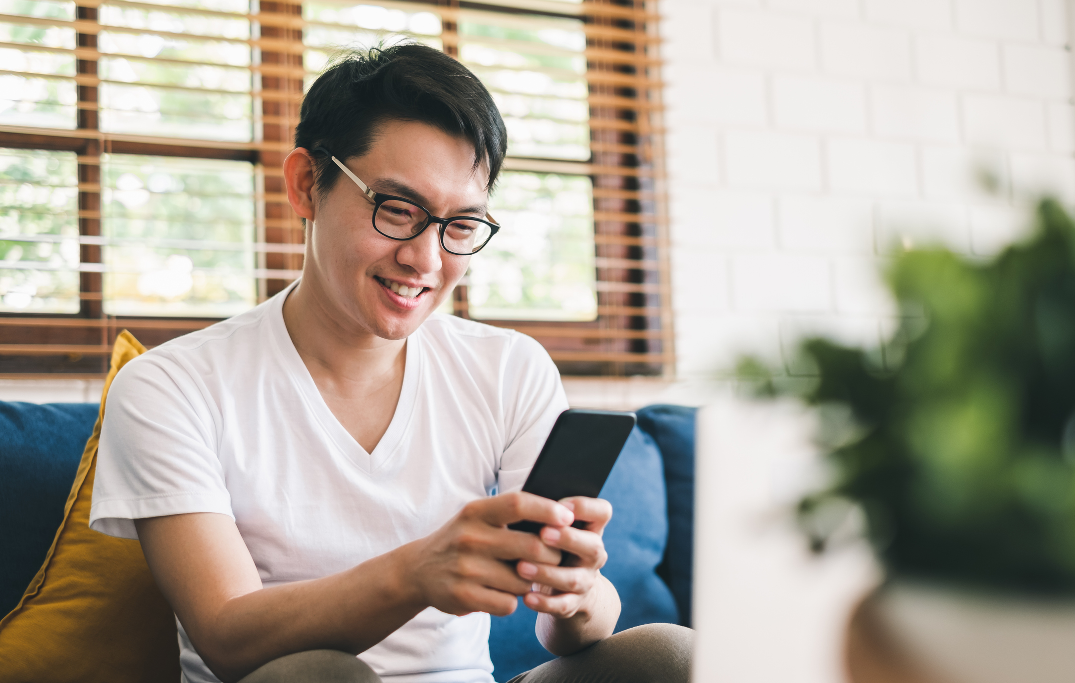 Stock photo of man sitting on sofa looking at his cell phone and smiling